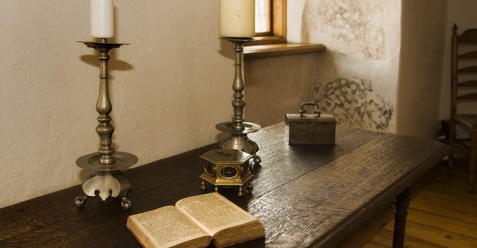 Saimnieka istabas galds ar grāmatu, galda pulksteni un svečturiem
