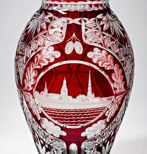 Vāze. Veltījums LPSR 10 gadu jubilejai, 1950. gads. Slīpējis V. Kuzņecovs. Pūsts pārvilktais stikls. Dekors slīpēts, pulēts, gravēts, kodināts. RVKM krājums.